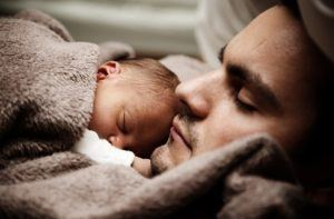 surviving the first month with a newborn- dad and baby sleeping
