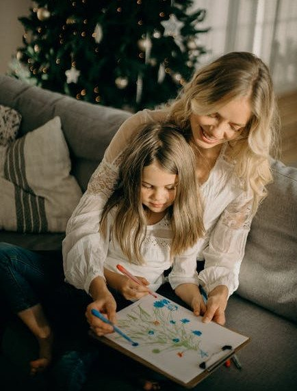 Easy DIY Christmas Ornaments for Kids- Toddler girl is sitting on mom's lap and both coloring Christmas Tree picture
