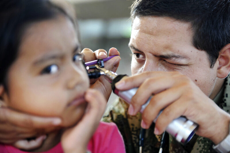 Doctor-checking-girl's-ear-using-otoscope