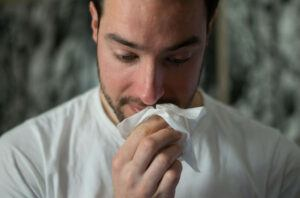man-wipes-nose-with-tissue