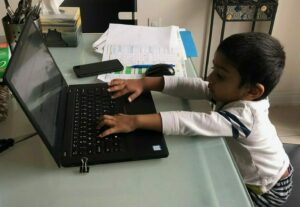 toddler-working-on-laptop-on-kitchen-table