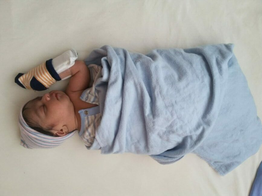 Newborn Breaks Out of a Swaddle -baby swaddled in blue blanket with one hand out