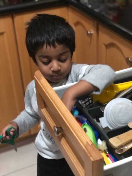 Baby Proofing Drawers and Cabinets Without Drilling-toddler getting something from the drawer