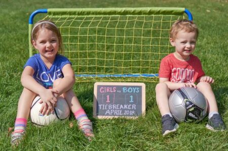 boy and girl holding soccer ball for pregnancy announcement