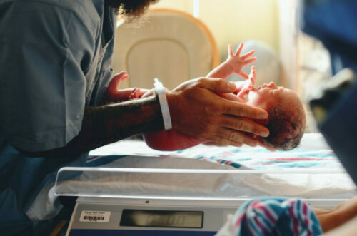 Is it harmful to Skip Meals during Pregnancy - doctor putting newborn on weigh scale