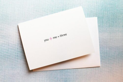 white card with 1+1 pregnancy announcement card
