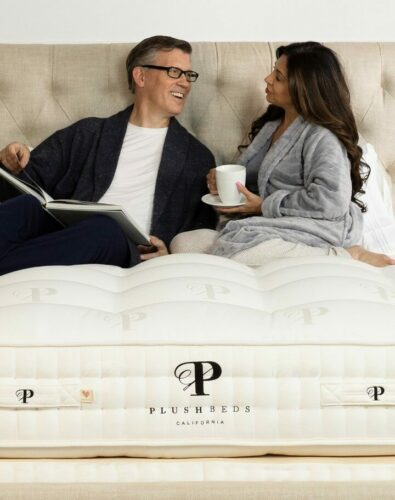 man and woman sitting and talking on a mattress