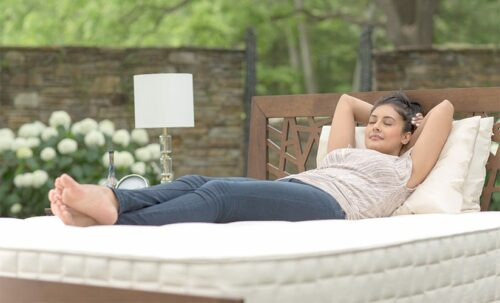 woman relaxing on a white mattress