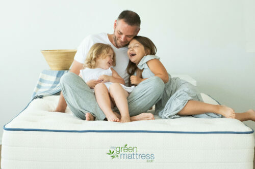 two kids are sitting on a dad's lap on a mattress