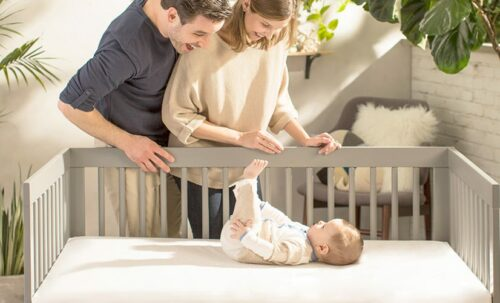 Naturepedic Crib Mattress Review: It is Worth the Money? - mom dad looking over a baby laying on a crib mattress