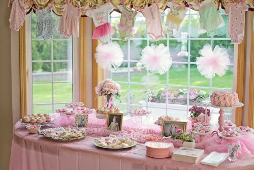 room decorated with pink baby onesies and pink treats for a home baby shower_places _to_host_a_baby_shower