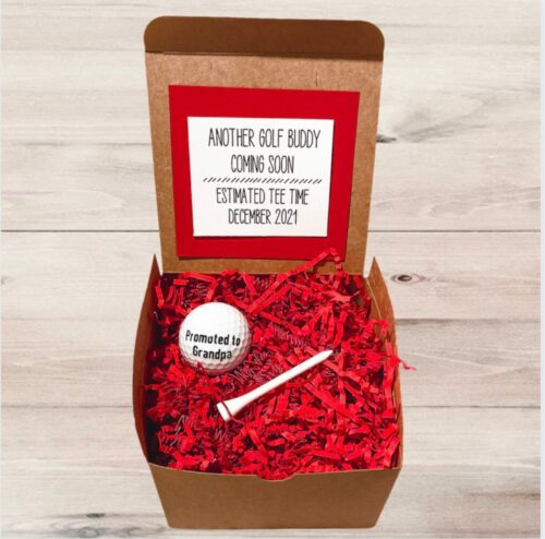 box with red filling and golt ball saying promoted to grandpa
