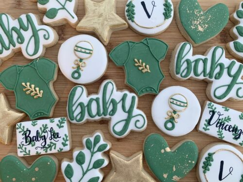 green cookie in shape of onesie, heart, and baby written on it